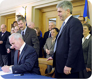 Governor Dayton signs legislation creating MNsure, pictured with the bill's chief authors Sen. Tony Lourey and Rep. Joe Atkins.